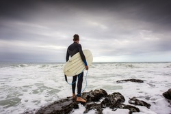 A surfer stands on the rocks with his surfboard  under his arm as he views the surf just before jumping in to the water