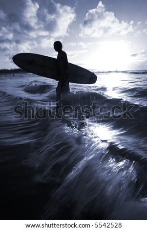 A surfer walks back in to the beach - focus is on wave breaking in front of him
