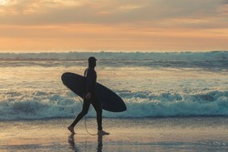 A surfer wearing a full body wet suit carries his board along the shore line as the sun sets.