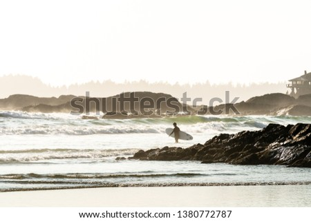 A surfer wearing a wetsuit entering the ocean carrying a surfboard, with rock outcroppings, islands, and a beach house in the misty background, Tofino, British Columbia, Canada.  #1380772787