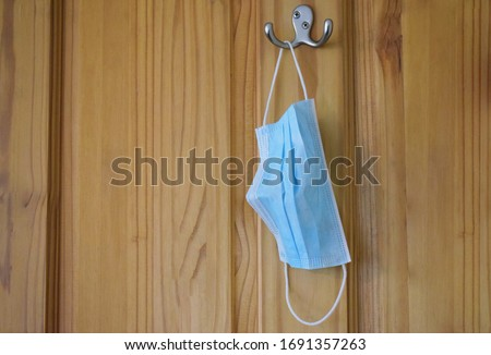 A surgical face mask used by a member of the public to protect against infection and spread  during the Corona virus / Covid19 health crisis hanging on a hook on the back of a door.  Foto stock ©