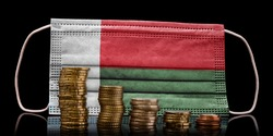 A surgical mask with the flag of Madagascar behind some descending stacks of various coins.(series)