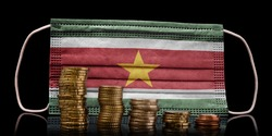 A surgical mask with the flag of Suriname behind some descending stacks of various coins.(series)