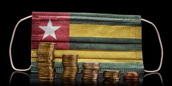 A surgical mask with the flag of Togo behind some descending stacks of various coins.(series)