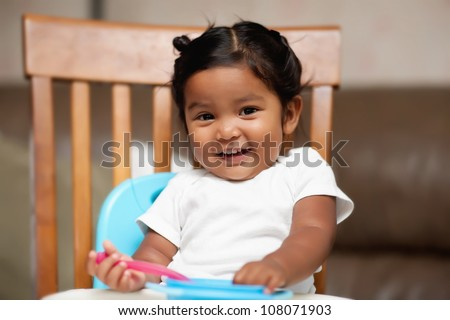 A surprised little girl holding a spoon and sitting in a high chair
