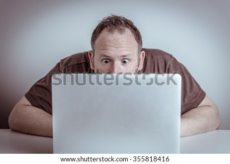 A surprised man with wide eyes sits hidden behind a laptop notebook computer staring at the screen with a shocked or frustrated expression on his face.
