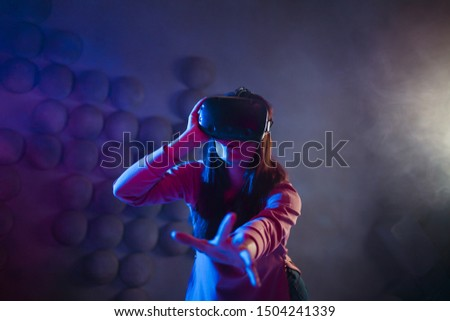 A surprised woman in virtual reality glasses touches the air with her hands, tries to find something, uses an invisible control panel on a dark background. Copyspace.