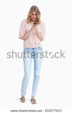 A surprised woman is standing up looking at her mobile phone against a white background