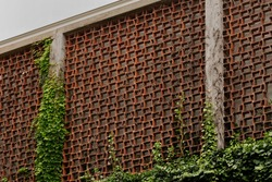 A surrounding wall with perforated red bricks and concrete columns, with climbing plants, in Ivrea, in Piedmont, Italy .Concept of 1960s architecture