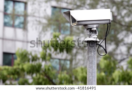 A surveillance camera monitoring road traffic with an office building in the background