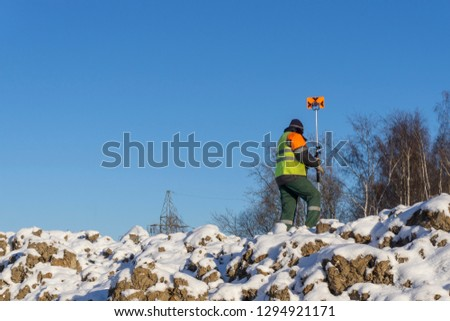 A surveyor's assistant with a measuring instrument conducts a topographical survey for cadastre
