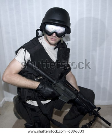 a swat police officer with helmet and m16machine gun