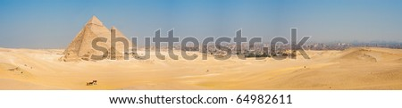 A sweeping panorama of the entire desert and all three of the Great Pyramids at Giza and the cityscape background of Cairo, Egypt nearby on a blue sky day.  Horizontal copy space