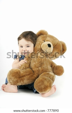 A sweet baby girl hugs her teddy and smiles