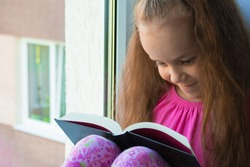a sweet, dark-skinned little girl in a pink T-shirt and shorts sits at home alone in quarantine on the window sill in the summer and reads a book with interest. Lok Down education. copy space