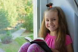 a sweet, dark-skinned little girl in a pink T-shirt and shorts sits at home alone in quarantine on the windowsill by the window and a book and looks at the camera. Lok Down education. copy space