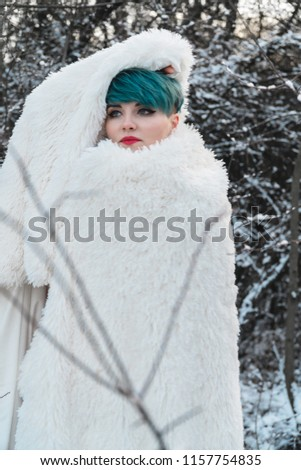 Stock Photo A sweet girl wrapped her head in a white fur coat, hiding from the cold in a winter snow-covered park