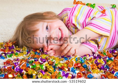 A sweet laughing kid lying among candies