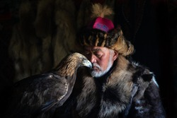 A sweet moment between an old kazakh eagle hunter and his majestic golden eagle indoors in dark traditional kazakh ger. Ulgii, Western Mongolia.