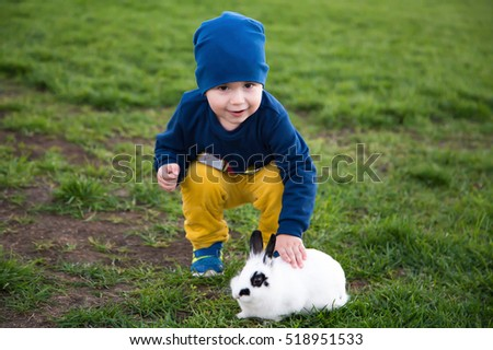 A sweet two years old boy is sitting with a small tiny rabbit. What a lovely photo for a family album!