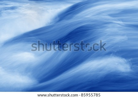 A swiftly moving stream in shades of blue.