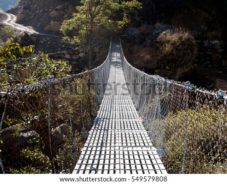 A swinging bridge over the creek in a canyon. #549579808