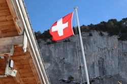 A Swiss flag blowing in the wind next to a wooden roof overhang with a mounted surveillance camera. Mountains in the background. Security concept. Banking secrecy.