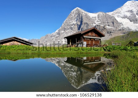 A Swiss Mountain Chalet Reflecting In A Calm Pond With The