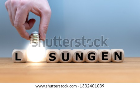 """A Symbol for finding a solution. Dice and a light bulb form the German word """"LÖSUNGEN"""" (""""SOLUTIONS"""" in English)."""