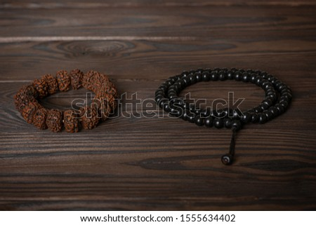 a symbols of religions, Islamic black rosary and a Buddhist bracelet lie together on a wooden table.  Religion Friendship Art Concept between Buddhism and Islam