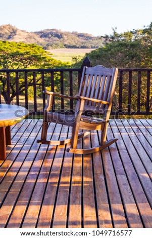 A table, a rocking chair in the open air. #1049716577