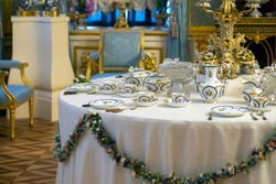 A table elegantly set for a grand tea party or other event with an elegant porcelain tea service on a snow-white tablecloth with flower garlands. Palace interior and rich decoration in classic style.