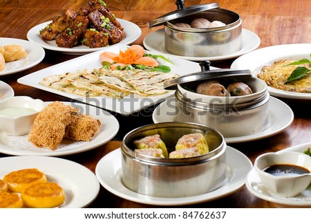 A table filled with plates of Chinese Dim Sum dumplings, cake, sticky rice and other delicious food.