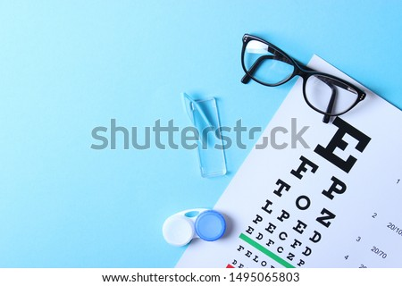 a table for checking vision, glasses and lenses for correcting vision on a colored background, top view. Ophthalmologist Accessories.