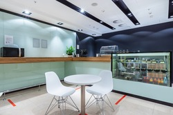A table for two at a light minimalistic canteen with a wooden counter and a microwave