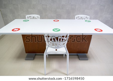 A table in a pantry of an office which only allows 3 people to have lunch which has check symbol stickers and cancel symbol stickers in pandemic for social distancing to avoid covid-19