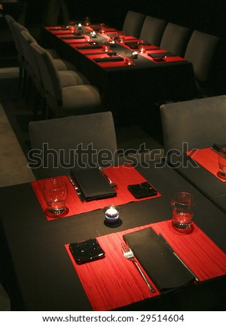 A table in a restaurant in Buenos Aires, red placemats in a black surrounding