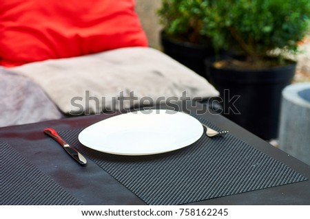 A table in a small restaurant is served for breakfast, lunch, dinner. White dish and cutlery - fork and knife. Sofa with soft cushions in the background. Beautiful wicker napkins on the table. #758162245