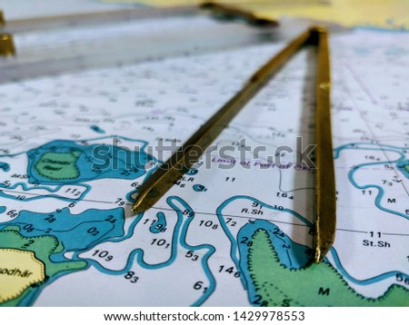 a table laid down with navigational chart compass divider and ruler for the purpose of navigation #1429978553