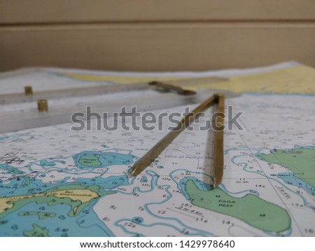 a table laid down with navigational chart compass divider and ruler for the purpose of navigation #1429978640