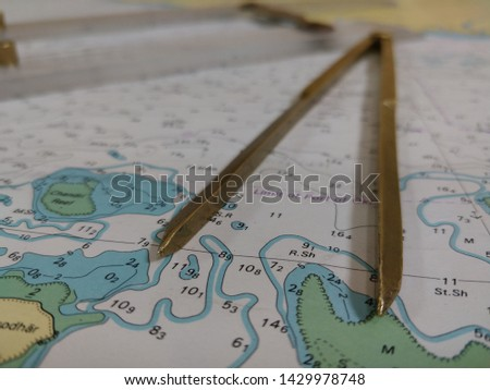 a table laid down with navigational chart compass divider and ruler for the purpose of navigation #1429978748