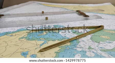 a table laid down with navigational chart compass divider and ruler for the purpose of navigation #1429978775