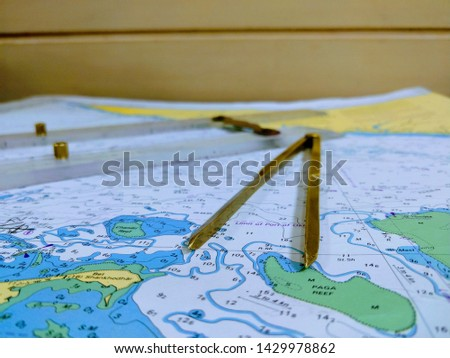 a table laid down with navigational chart compass divider and ruler for the purpose of navigation #1429978862