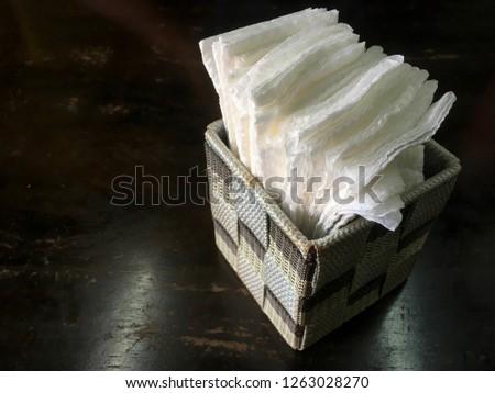 A table napkin holder with napkin.