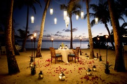 A Table Set up for a romantic meal on the beach with lanterns and chairs and flowers with palms and sky and sea in the background
