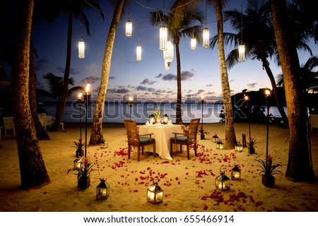 Photo of  A Table Set up for a romantic meal on the beach with lanterns and chairs and flowers with palms and sky and sea in the background