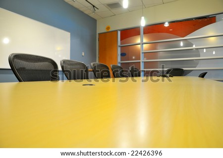 a table side view of a long conference room with phone