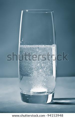 A tablet in a glass of water - stock photo