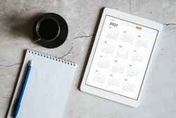 a tablet with an open calendar for 2021 year, a cup of coffee, and a spring notebook with a pen on a gray concrete background