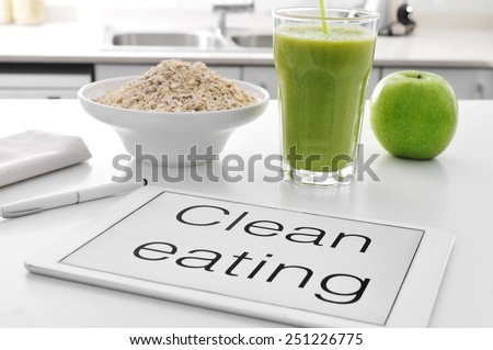 a tablet with the text clean eating written in it and a bowl with oatmeal cereal, a glass with a green smoothie and an apple on the kitchen table